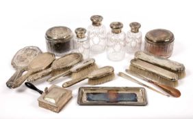 Four late 19th / early 20th century continental white metal topped cut glass bottles, a matching
