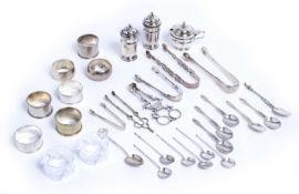 A collection of silver items to include coffee spoons, a pair of pierced sugar tongs by Hester