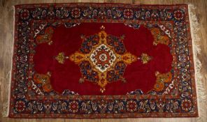Red ground rug with central foliate design and blue floral border, 123cm x 198cmCondition report: At