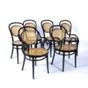 Set of six ebonised bentwood dining chairs in the manner of Thonet, each with caned seat and back,