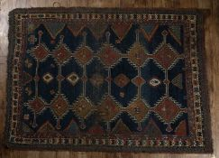 Hamadan blue ground rug with panels of stylised designs, within a geometric border, 177cm x