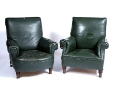 A matched pair of early 20th century library armchairs upholstered in green leather, one with rolled