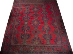 An old Turkey Oushak carpet with repeating blue and green medallion motif on a red ground, 365 x