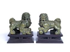 A pair of 20th century soapstone Temple Dogs after the Antique, each on a wooden plinth, 19cm