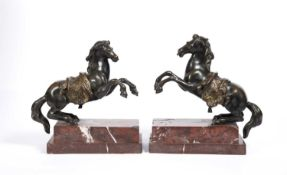 A pair of 18th century French bronze rearing horses, with gilt bronze saddles on red stepped