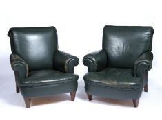 A matched pair of early 20th century library armchairs upholstered in green leather with rolled