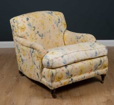A Howard style deep armchair standing on turned tapering front legs and brass casters, 84cm wide x