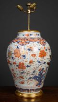 An antique porcelain large baluster jar converted to a table lamp, in imari colors, the white ground