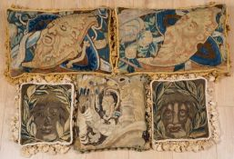 A pair of 17th century tapestry fragments used as cushions, each decorated with bearded masks and