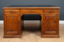 An early 20th century walnut partners desk with black leather inset top, panelled sides and with