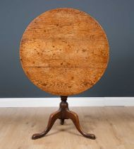 A George III oak circular tilt top tripod table with turned column support, 82cm diameter x 71.5cm