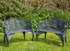 A pair of green painted cast iron garden benches with mask terminals to the arms, the backs with