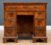A George II walnut and featherbanded kneehole desk, with seven drawers about the knee and central