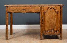 A French oak desk with single drawer and cupboard enclosing three drawers within and also with slide