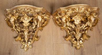 A pair of 19th century continental gilt carved wood wall brackets decorated with cherubs