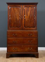 A George III mahogany press cupboard with secretaire drawer, the upper section with decorative