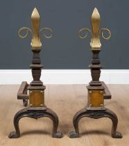 A pair of Victorian brass and cast iron fire dogs, with embossed fleur-de-lis form finials on curved