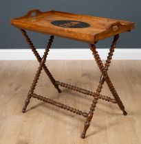 A Victorian olive wood tray complete with folding bobbin turned stand, the quarter veneered tray
