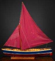 A model sailing boat on stand, the blue and red painted hull constructed from various woods and
