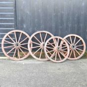 A pair of red painted wooden cartwheels,