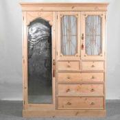 An Edwardian stripped pine combination wardrobe,