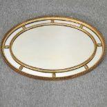 An early 20th century gilt framed oval wall mirror