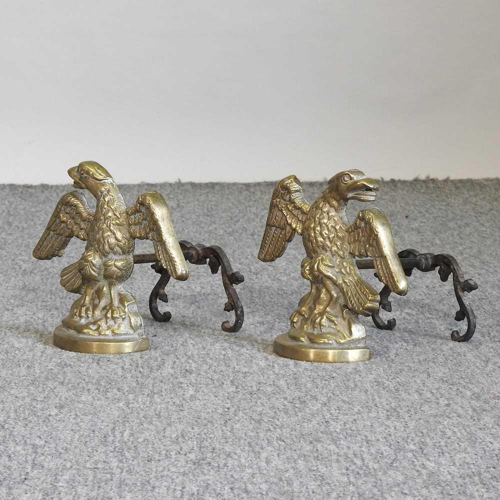 A pair of brass fire dogs