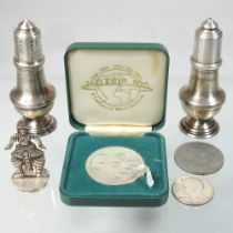 A pair of early 20th century silver peppers