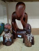A carved wood figure of 'the thinking man' and a carved pair of African busts