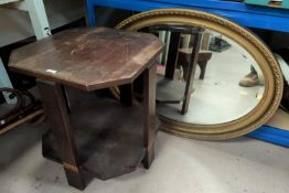 A gilt framed oval bevelled edge wall mirror; a canted 2 tier Art Deco oak occasional table