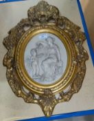 A reproduction relief wall plaque, woman and cherub, in ornate gilt frame