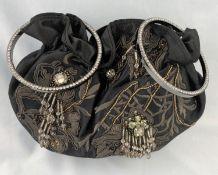 A Karen Millen evening handbag with twin circle diamante handles, tube line body decoration with