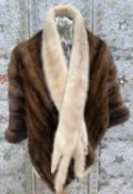 A brown mink short jacket, a blonde mink scarf, a bowler hat
