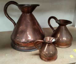 A 19th century matched set of three graduating copper measuring jugs, the smaller of the three
