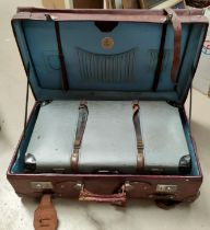 A large strapped leather suitcase; a compressed card suitcase