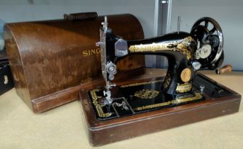 An early 20th century hand operated sewing machine in walnut case