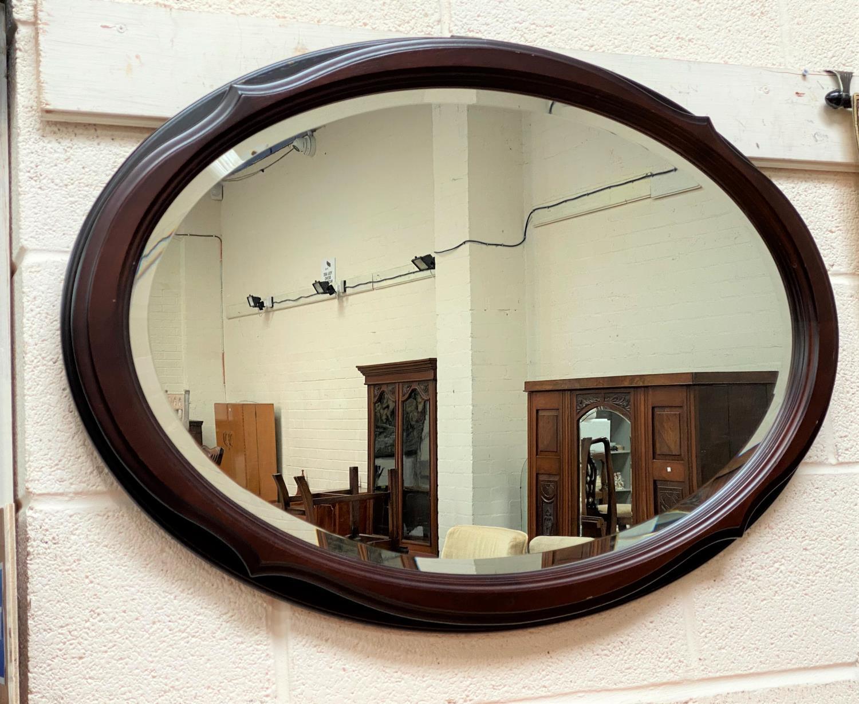 A mahogany framed oval mirror