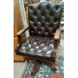 An office swivel armchair with deep button back leather effect upholstery and studded edging