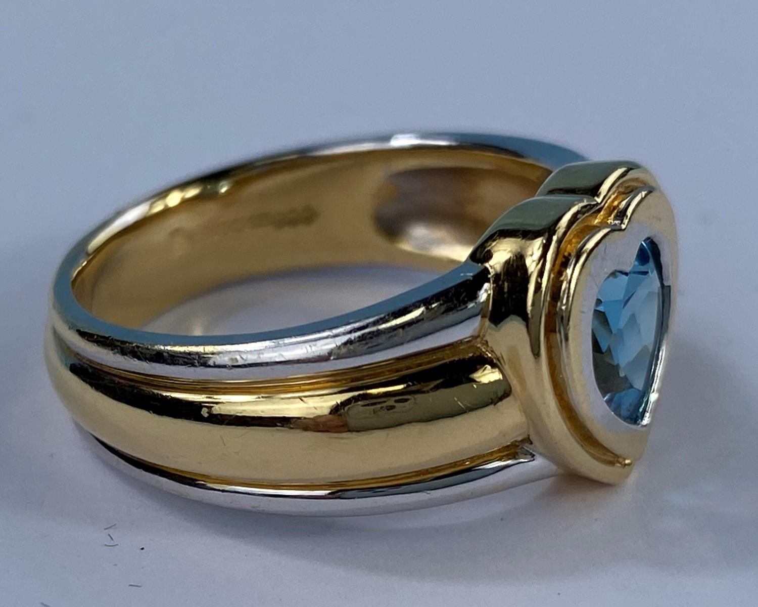A lady's 18ct hallmarked two tone gold dress ring on a broad shank and blue stone in heart - Image 5 of 6