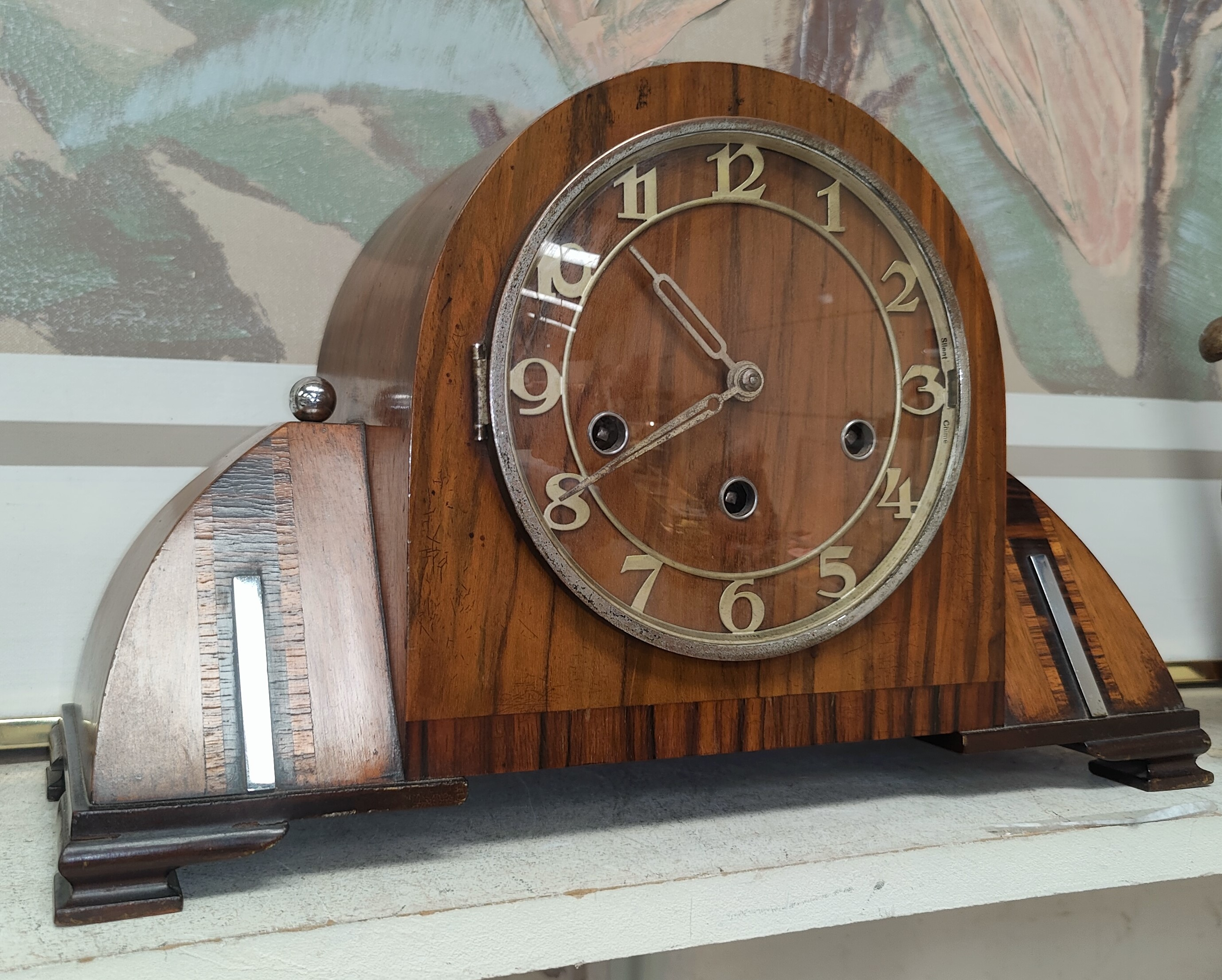 A stylish Art Deco walnut mantel clock with inlaid decoration and chrome mounts (with pendulum and