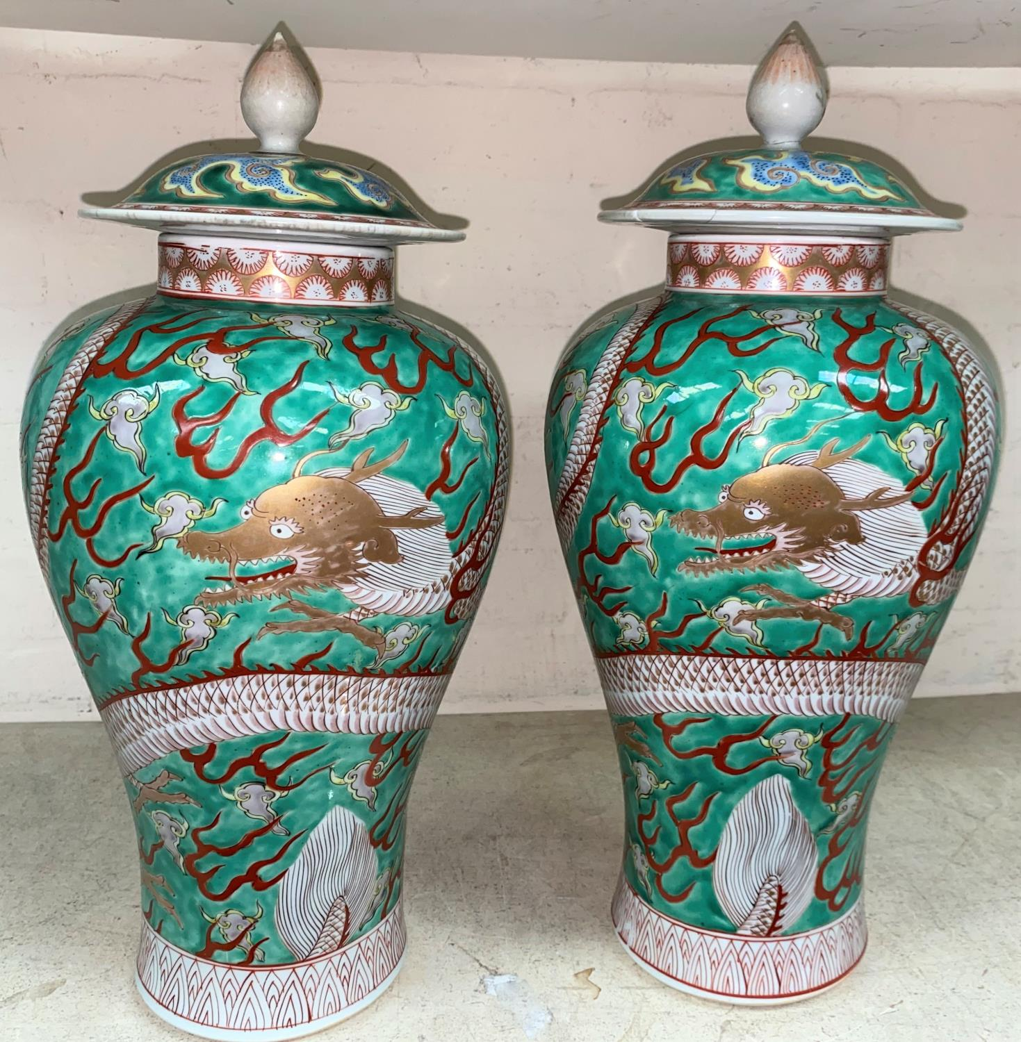 A pair of Chinese green ground lidded baluster vases with dragon decoration lids bearing marks,