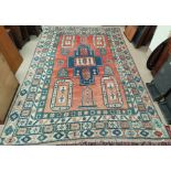 A modern Persian style carpet, hand knotted with geometrical design on a red ground, 350 x 120 cm