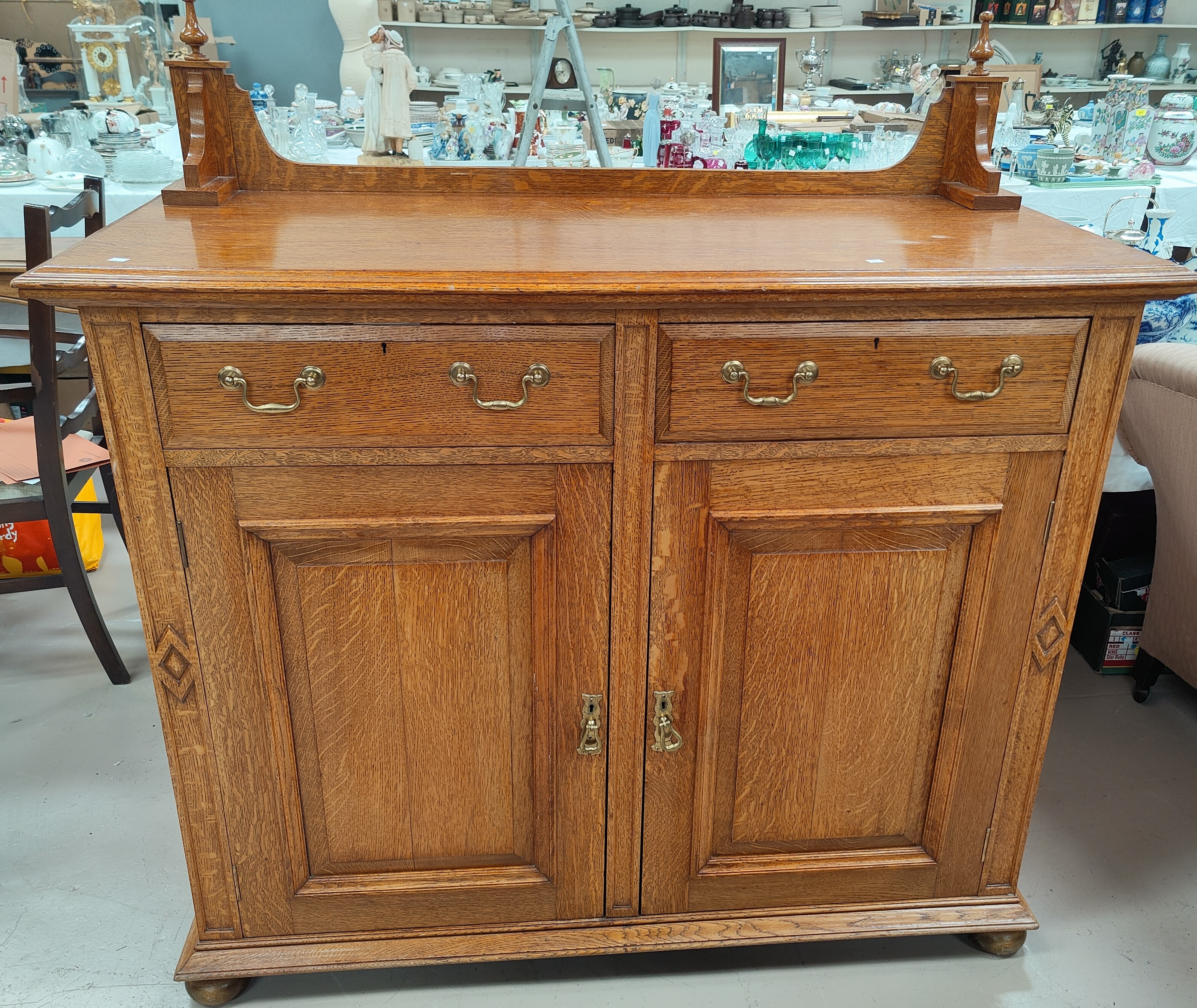 A large Golden Oak sideboard/side cabinet with doubled paneled doors, two drawers with brass drop