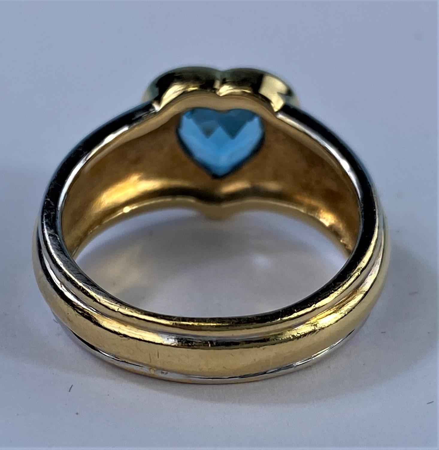 A lady's 18ct hallmarked two tone gold dress ring on a broad shank and blue stone in heart - Image 6 of 6