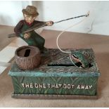 """A vintage American cast iron money box with painted decoration """"The One That Got Away"""" 17cm"""