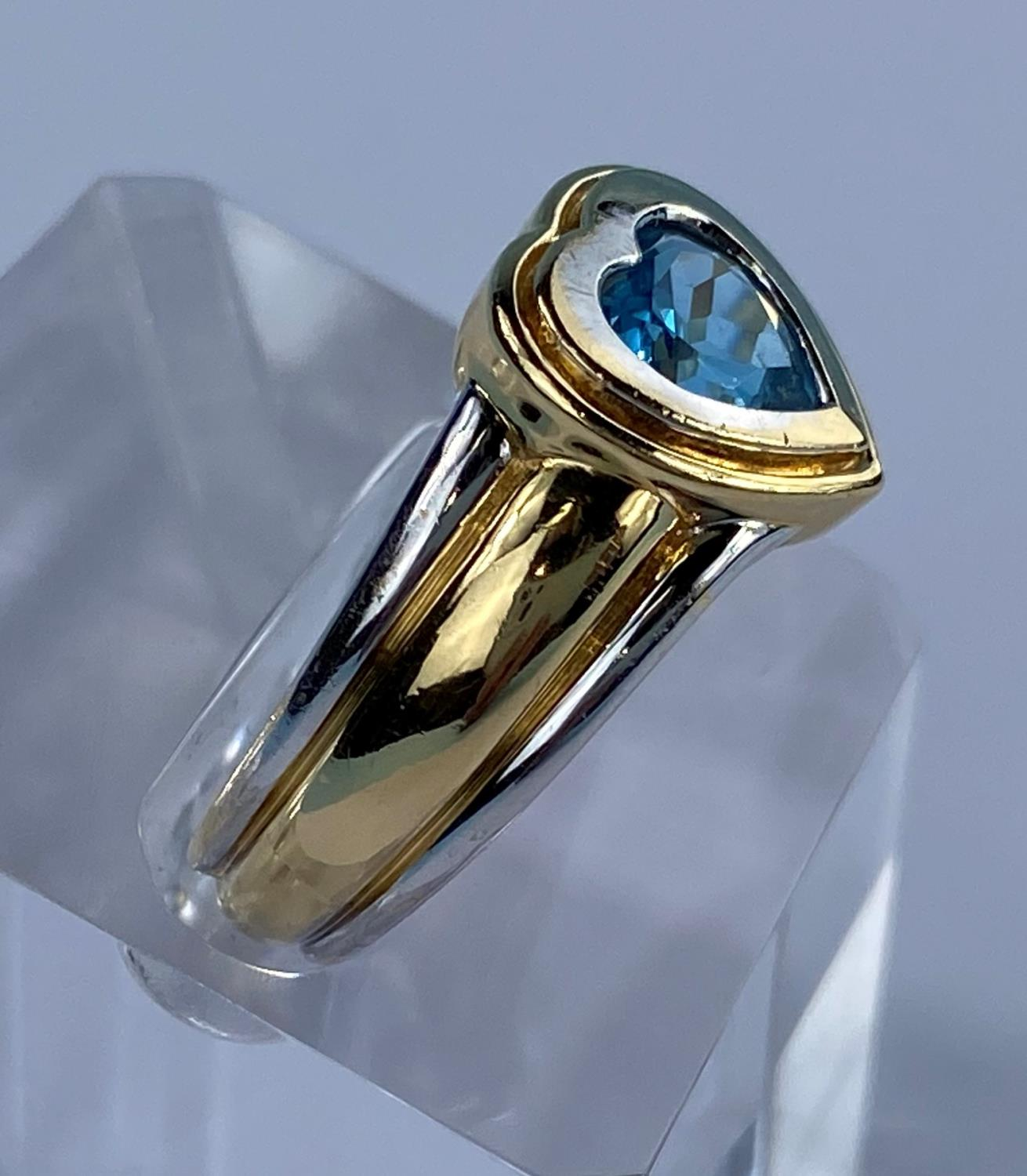 A lady's 18ct hallmarked two tone gold dress ring on a broad shank and blue stone in heart - Image 4 of 6