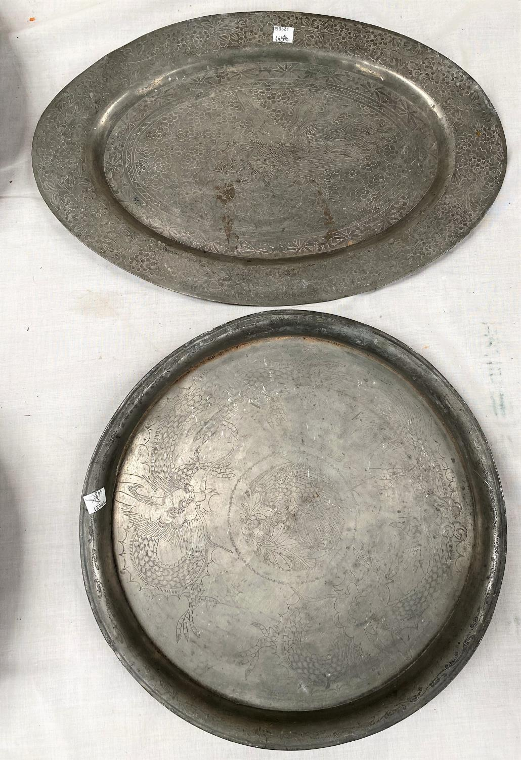 Two 20th century Chinese pewter trays - circular one with dragons, oval with mythical bird, 34cm x