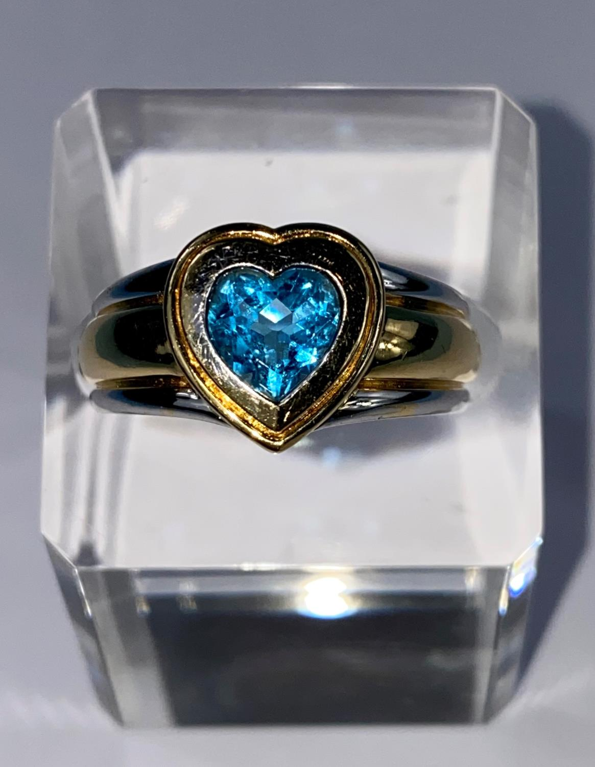 A lady's 18ct hallmarked two tone gold dress ring on a broad shank and blue stone in heart