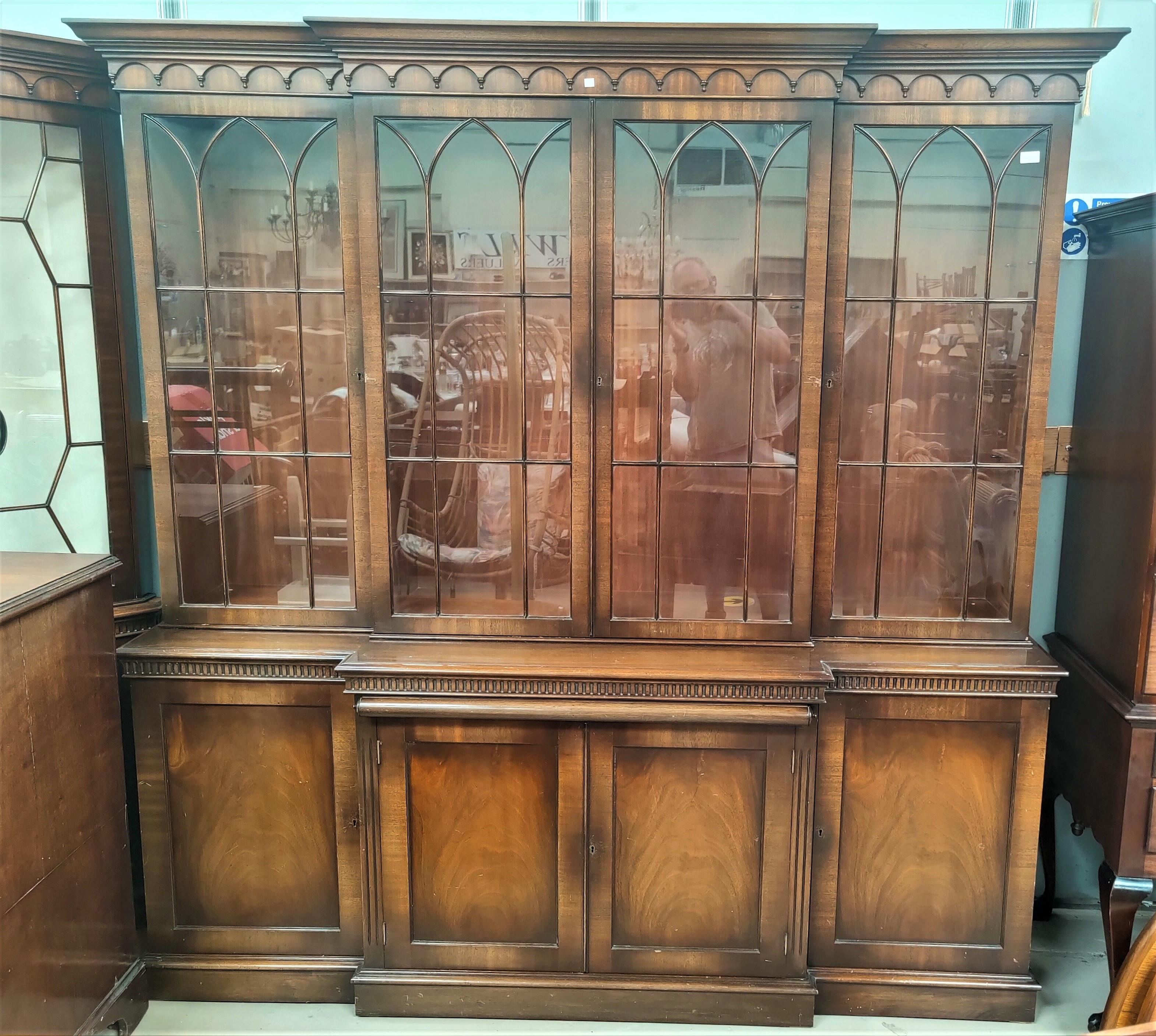 """A Georgian style mahogany break front library bookcase in the manner of """"Reprodux"""" by Bevan &"""
