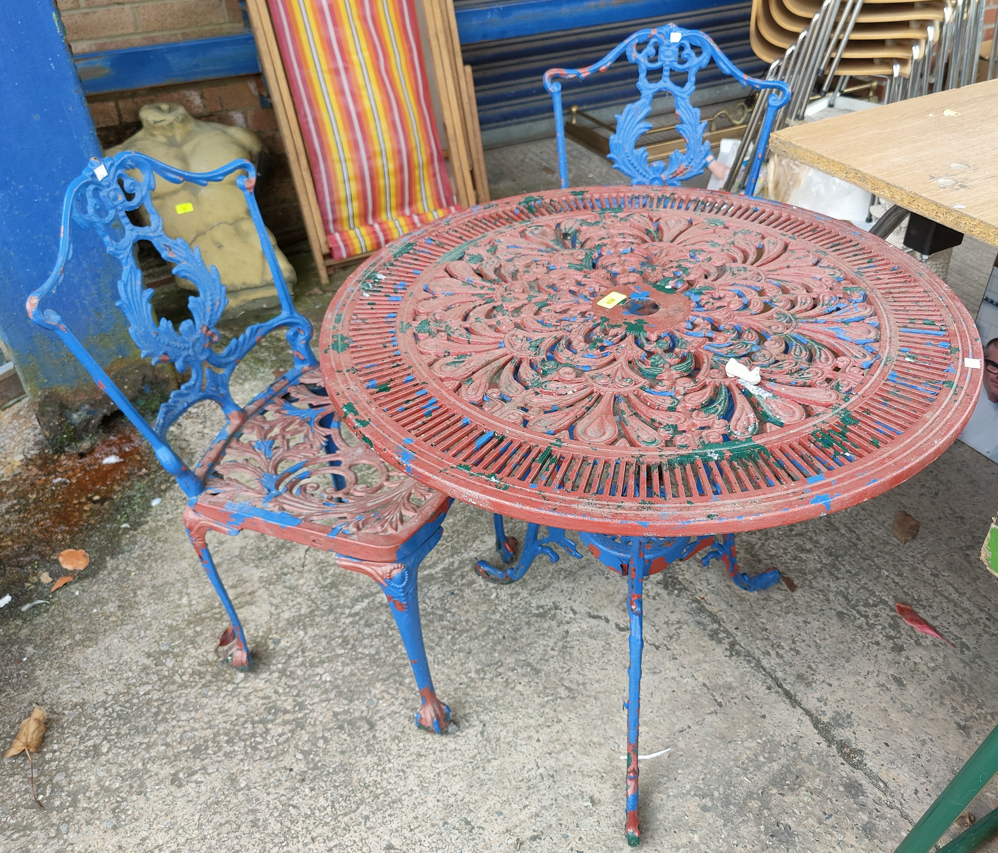 A Victorian style cast metal circular garden table and two chairs